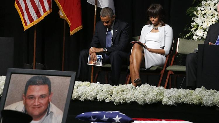 President Barack Obama and first lady Michelle Obama bow their heads behind a photo of volunteer firefighter Capt. Cyrus Adam Reed, who was killed, as they attend the memorial for victims of the fertilizer plant explosion in West, Texas, Thursday, April 25, 2013, at Baylor University in Waco,Texas. (AP Photo/Charles Dharapak)