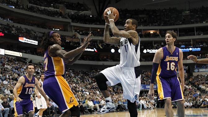 Dallas Mavericks guard Monta Ellis leaps to the basket for a shot attempt as Los Angeles Lakers' Jordan Hill, left, defends in the second half of an NBA basketball game, Tuesday, Nov. 5, 2013, in Dallas. Lakers' Steve Nash (10) and Pau Gasol (16) watch. Ellis led the scoring with 30 points in the 123-104 Mavericks win