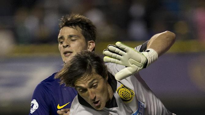 Rosario Central's goalkeeper Mauricio Caranta, right, vies for the ball with Boca Juniors' Federico Bravo during an Argentina's league soccer match in Buenos Aires, Argentina, Sunday, Oct. 13, 2013