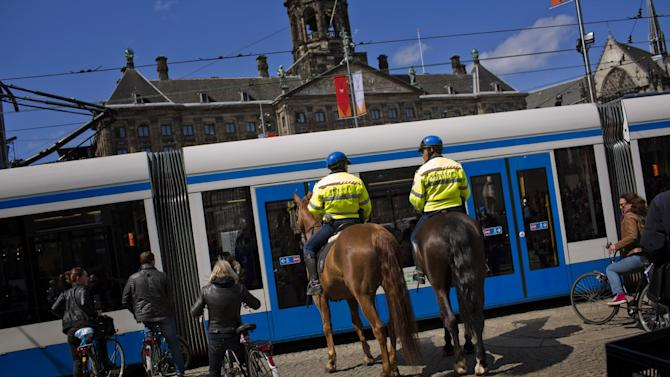 Mounted police officers patrol in downtown Amsterdam, Netherlands Monday, April 29, 2013. Queen Beatrix has announced she will relinquish the crown on April 30, 2013, after 33 years of reign, leaving the monarchy to her son Crown Prince Willem Alexander. (AP Photo/Emilio Morenatti)