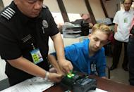 Thomas van Beersum has his fingerprint taken at the immigration office of Manila Airport on August 6, 2013. He has been deported and banned from the country after being photographed apparently making a policeman cry during an anti-government protest