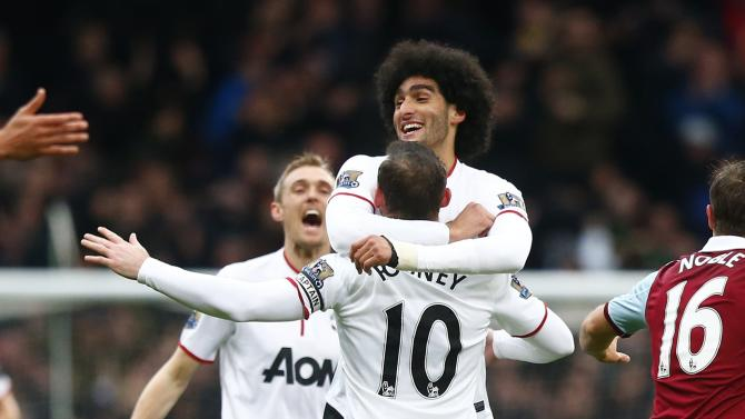 Manchester United's Rooney celebrates with team mate Fellaini after scoring a goal against West Ham United during their English Premier League soccer match at the Boleyn Ground in London