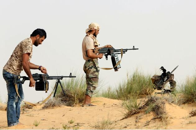 Fighters from the Fajr Libya (Libya Dawn) militia load their weapons during clashes with forces loyal to Libya's internationally recognised government, southwest of Sabratha on May 25, 2015