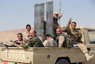Iraqi Kurdish Peshmerga fighters celebrate sitting on the back of a truck as they head to the Mosul dam on the Tigris river that they recaptured from Islamic State jihadists on August 17, 2014 near the northern Iraqi city of Mosul