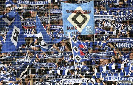 A Hamburg SV supporter waves a flag in the stands ahead of their German Bundesliga first division soccer match against Schalke 04 in Hamburg