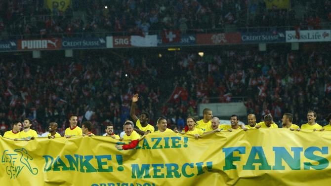 Switzerland's players hold a banner thanking their supporters as they celebrate defeating Slovenia during 2014 World Cup qualifying soccer match in Bern