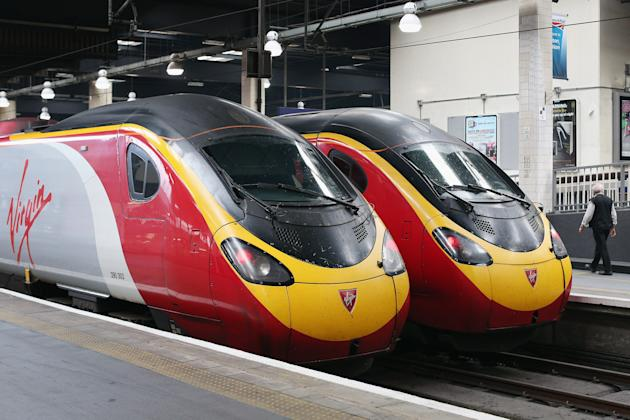 LONDON, ENGLAND - AUGUST 15: Virgin trains prepare to depart from Euston Station on the West Coast Mainline route on August 15, 2012 in London, England. Virgin Rail has been outbid by FirstGroup, UK's largest train operator, to continue running the West Coast Mainline franchise which it has done for the past 15 years. FirstGroup bid 5.5 billion GBP to run the lucrative route between London and Scotland via the West Midlands that serves 31 million passengers annually. FirstGroup will take control of the franchise from December 9, 2012 and are due to to operate the service until 2026. (Photo by Oli Scarff/Getty Images)