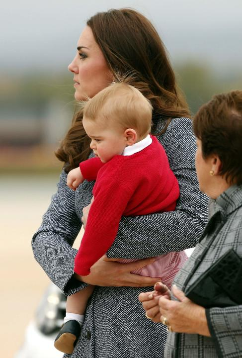 Britain's Catherine, the Duchess of Cambridge, holds her son Prince George as they prepare to board a plane with her husband Prince William to depart Canberra
