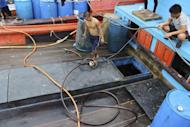 In this photo taken Wednesday, June 10, 2015 and released by the Government of the Republic of Palau, Vietnamese fishermen work on their fishing ship anchored at the Marine Law Enforcement Division Port in Koror, Palau after being caught fishing illegally in the waters of the country. The tiny Pacific nation of Palau, fighting a rising tide of illegal fishing in its waters, has set fire to four boats of Vietnamese caught poaching sea cucumbers and other marine life in its waters. Palau's president, Tommy Remengesau Jr., said the boats were burned Friday morning, June 12, 2015. He hopes to turn most of the island nation's territorial waters into a national marine sanctuary, banning commercial fishing and exports apart from limited areas to be used by domestic fishermen and tourists. (The Government of the Republic of Palau via AP)