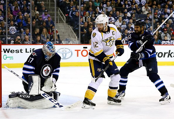 WINNIPEG, MB - NOVEMBER 27: Mike Fisher #12 of the Nashville Predators creates a screen in front of goaltender Connor Hellebuyck #37 of the Winnipeg Jets as the puck flies towards the net during third period action at the MTS Centre on November 27, 2016 in Winnipeg, Manitoba, Canada. (Photo by Darcy Finley/NHLI via Getty Images)