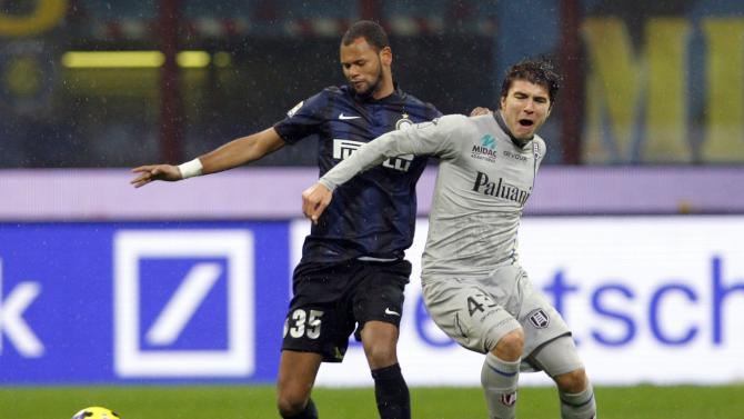 Inter Milan's Rolando fights for the ball with Chievo's Paloschi during their Italian Serie A soccer match in Milan