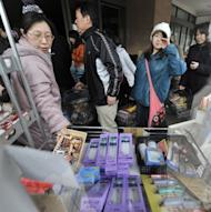 People are seen queuing to buy food and supplies at a supermarket in Kitakami, Iwate prefecture, in 2011. The weak pulse of Japan's economic recovery has slowed again, with mixed figures showing it is struggling to achieve momentum