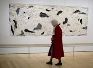 """A woman views a painting titled """"Yellow River"""" by Chinese artist Wu Guanzhong at the Asia Society in New York. The first major US retrospective of Chinese artist Wu will fulfill the painter's dying wish to be better known in the West -- and signaling the continued rise of Chinese art on the international stage"""