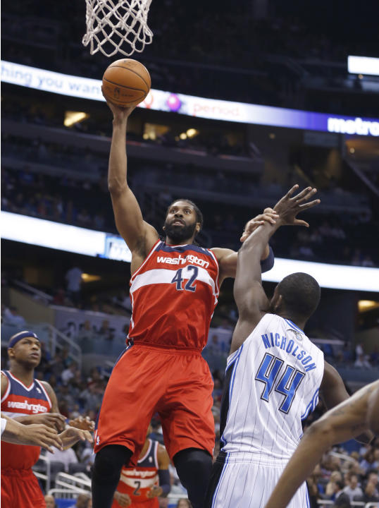 Washington Wizards forward Nene Hilario of Brazil (42) shoots over Orlando Magic forward Andrew Nicholson of Canada (44) during the first half of an NBA basketball game in Orlando, Fla., on Friday, Ap