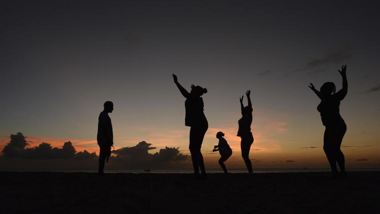 Women exercise in front of a trainer as the sun sets near Kensington Oval in Bridgetown, Barbados
