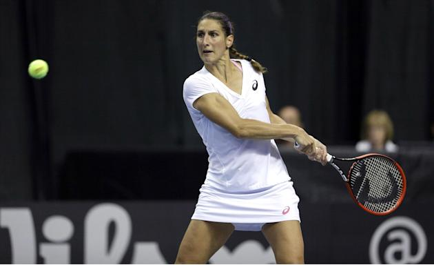 France's Virginie Razzano returns a ball to United States' Sloane Stephens during a Fed Cup singles world group playoff tennis match on Sunday, April 20, 2014, in St. Louis