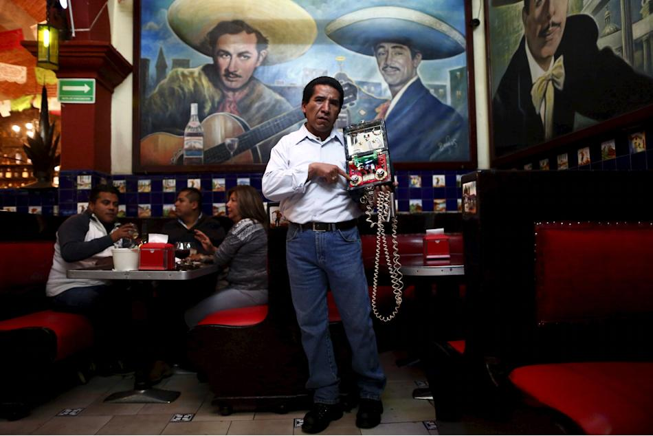 A toquero poses for a photo with his machine that gives electric shocks, inside Tenampa restaurant at Garibaldi square in Mexico City
