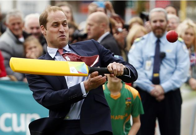 Britain's Prince William reacts as he tries to hit a ball using a cricket bat as he and his wife Catherine, the Duchess of Cambridge, attend a promotional event for the upcoming Cricket World Cup