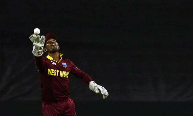 West Indies wicket keeper Denesh Ramdin tosses the ball in the air after catching out India's Rohit Sharma during their Cricket World Cup match in Perth