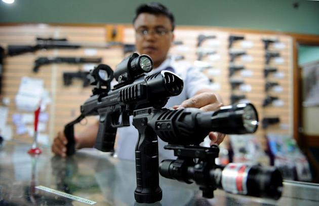 A salesman at a weapons shop in Manila demonstrates how to use a conversion kit on a 9mm handgun on April 4, 2013. The proliferation of firearms in the Philippines has been in the spotlight following a series of shooting-related deaths