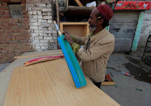 A carpenter repairs a cricket bat at his workshop in Islamabad