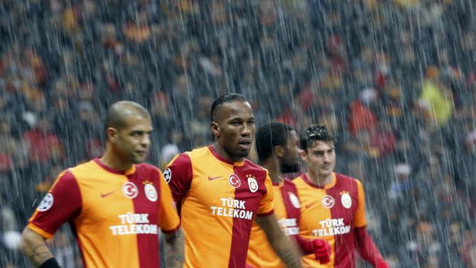 Drogba of Galatasaray and team mates react as their match against Juventus is put on hold ahead of a pitch inspection.