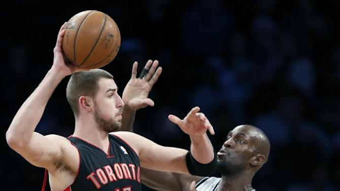 Toronto Raptors center Jonas Valanciunas (17) passes around Brooklyn Nets forward Kevin Garnett (2) in the first half of an NBA basketball game, Monday, Jan. 27, 2014, in New York