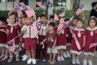 Schoolchildren wave Malaysian flags during the arrival of Britain's Prince William and his wife Catherine, the Duchess of Cambridge, at the Hospis Malaysia in Kuala Lumpur on September 13. The couple's marriage in April 2011 was watched by up to two billion TV viewers around the world