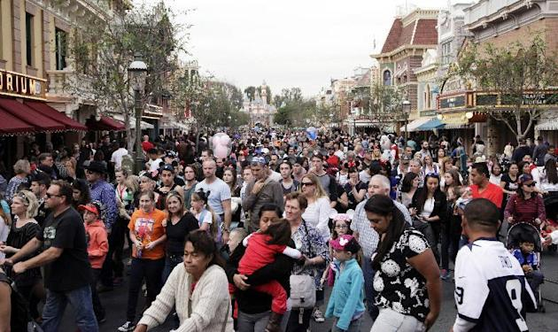 FILE - In this Jan. 22, 2015, file photo, people crowd Main Street at Disneyland in Anaheim, Calif. California health officials have declared an end to the large measles outbreak that originated at Di