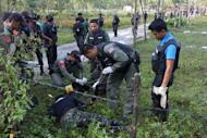 Police inspect the bodies of suspected insurgents who were killed when they attacked a military base in Thailand's restive southern province of Narathiwat on February 13, 2013. Scores of heavily armed gunmen stormed the military base, an army spokesman said, in a major assault that left at least 16 militants dead