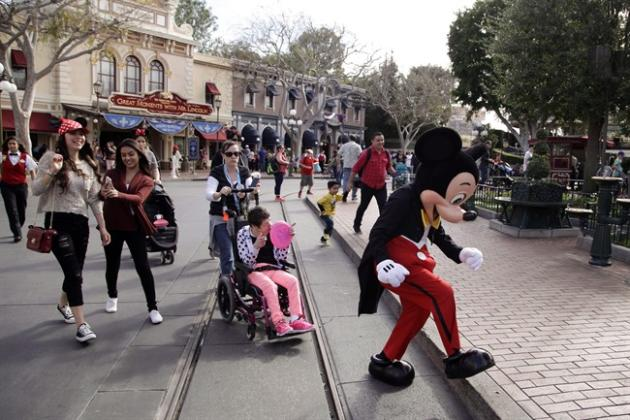 Visitors follow Mickey Mouse for photos at Disneyland, Thursday, Jan. 22, 2015, in Anaheim, Calif. Testing shows there is no link between four recent measles cases in Toronto and a large outbreak linked to the Disneyland theme parks in California. THE CANADIAN PRESS/AP/Jae C. Hong