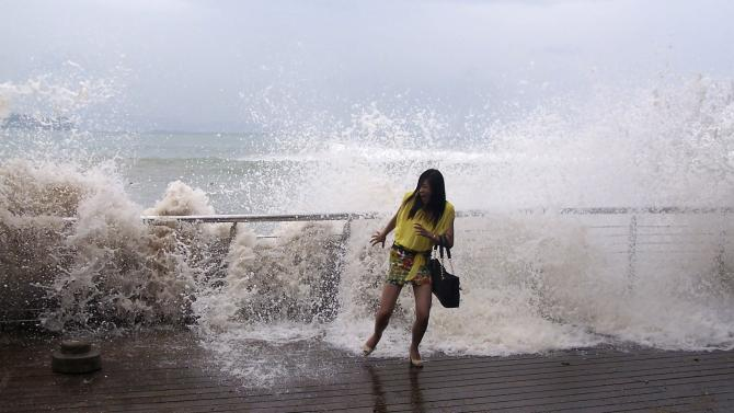 A woman reacts as a storm surge past a barrier on the shore as Typhoon Usagi approaches Shenzhen