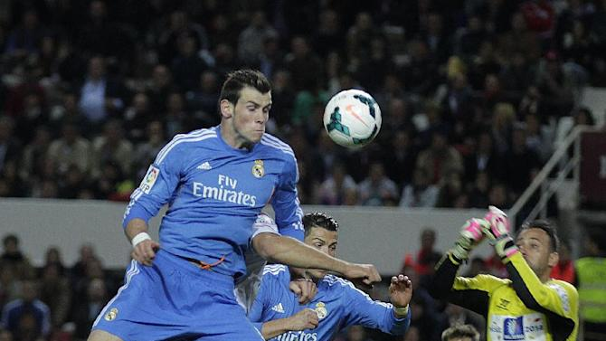 Real Madrid's Gareth Bale from Wales, top, jumps for the ball against Sevilla during their La Liga soccer match at the Ramon Sanchez Pizjuan stadium, in Seville, Spain, Wednesday, March 26, 2014