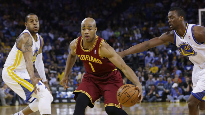 Cleveland Cavaliers guard Jarrett Jack (1) dribbles between Golden State Warriors forward Andre Iguodala, left, and Harrison Barnes (40) during the first half of an NBA basketball game on Friday, March 14, 2014, in Oakland, Calif