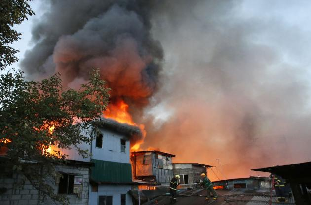 Firemen try to extinguish a fire in a squatter colony in Quezon city, Metro Manila