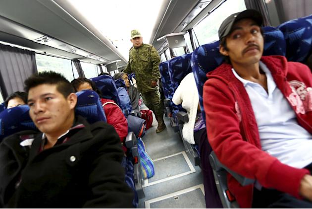 A soldier inspects a passenger bus at a checkpoint on an access highway to Mexico City