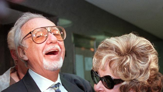 In an April 25, 1997, file photo Burt Pugach laughs with his wife, Linda, in the hallway of the Queens Criminal Court in New York, where Pugach was on trial for threatening another, younger woman, after she left him. Linda Pugach, who was blinded in 1959 when her future husband hired  men to throw lye in her face, died Tuesday, Jan. 22, 2013 in New York. She was 75.  (AP Photo/Emile Wamsteker, file)