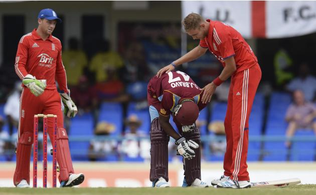 England's Broad and team mate Buttler check on West Indies' captain Bravo after he was struck by a bouncer during the second one-day international cricket match at North Sound