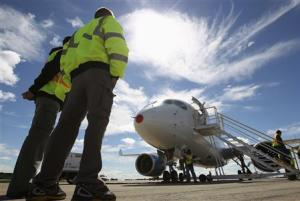 Bombardier employees look at the CSeries aircraft, after its first test flight in Mirabel, Quebec