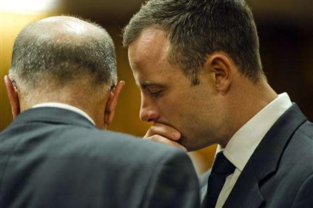 Olympic and Paralympic track star Oscar Pistorius speaks to his uncle Arnold Pistorius during the fifth day of his trial for the murder of his girlfriend Reeva Steenkamp at the North Gauteng High Court in Pretoria