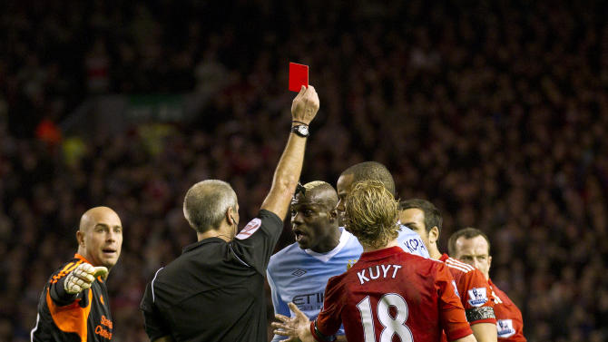 Manchester City's Mario Balotelli, center, is sent off by referee Martin Atkinson after a second yellow card during his team's 1-1 draw against Liverpool in their English Premier League soccer match at Anfield Stadium, Liverpool, England, Sunday Nov. 27, 2011. (AP Photo/Jon Super)