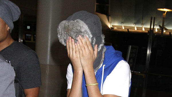 Justin Bieber playfully covers his face wearing matching blue vest & shoes and in sweats as he makes his way through LAX.