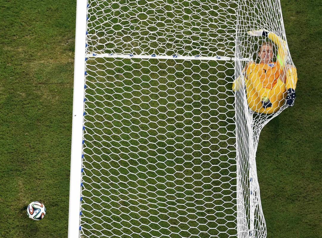 England's goalkeeper Hart rolls inside the goalpost after Italy's Balotelli scored during their 2014 World Cup Group D soccer match at the...