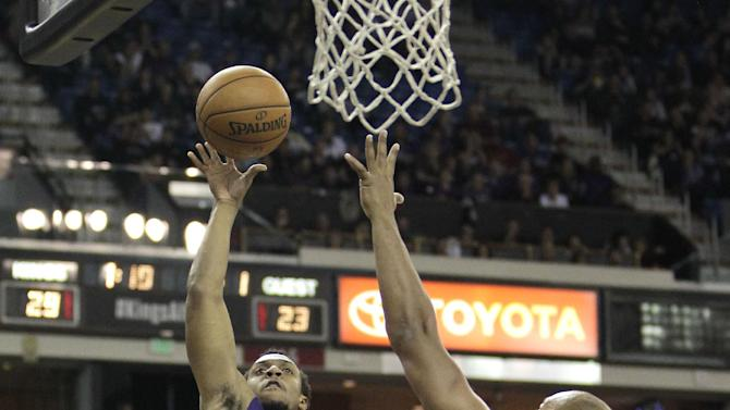 Phoenix Suns guard Ish Smith, left, shoots over Sacramento Kings forward Chuck Hayes during the first quarter of an NBA basketball game in Sacramento, Calif., Tuesday, Nov. 19, 2013