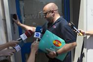 A man wearing a shirt with a Swiftair logo and carrying a Swiftair folder enters the Spanish airline's office in Madrid, Spain, Thursday, July 24, 2014. An Air Algerie flight carrying 116 people from Burkina Faso to Algeria's capital disappeared from radar early Thursday over northern Mali, officials said. The flight was being operated by Spanish airline Swiftair, the company said in a statement, and the plane belonged to Swiftair. The flight crew was Spanish. (AP Photo/Paul White)