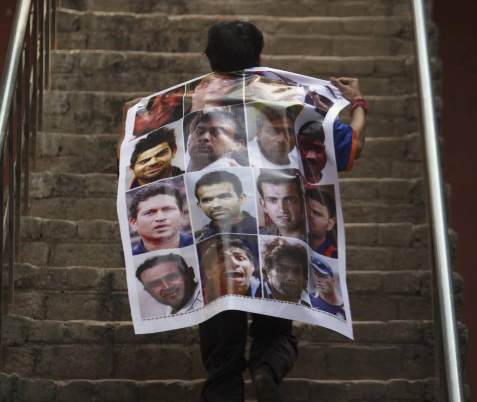 An Indian cricket team supporter carrying a poster displaying photographs of Indian cricket team members rushes up the stairs as he arrives to cheer for the Indian team in Jammu, India, Tuesday, March