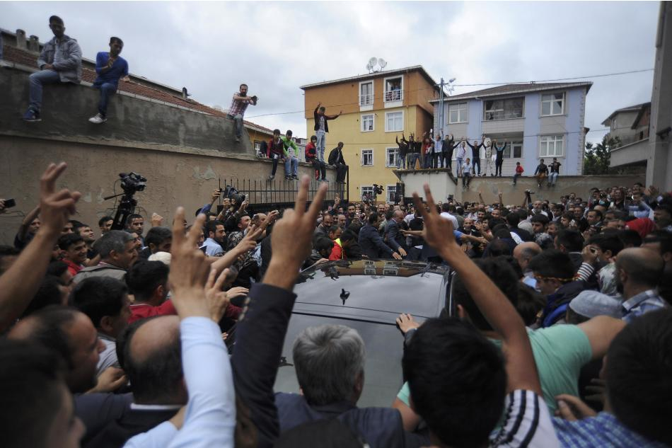 Supporters of Demirtas, co-chairman of the pro-Kurdish Peoples' Democratic Party (HDP) wave as he leaves a polling station during the parliamentary election in Istanbul