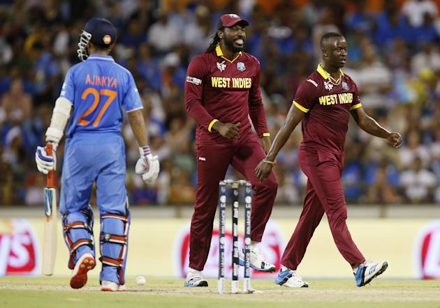 West Indies bowler Kemar Roach, right, celebrates with teammate Chris Gayle, centre, after dismissing Indian batsman Ajinkya Rahane, left, during their Cricket World Cup Pool B match in Perth, Austral
