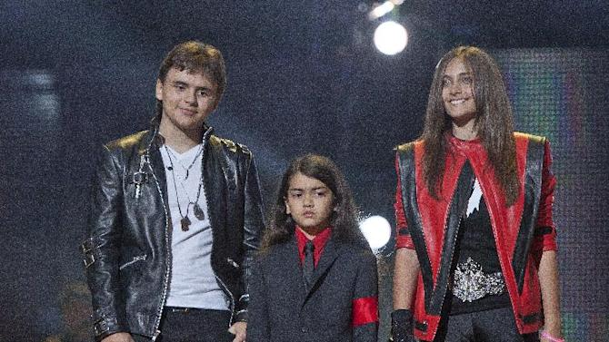 "FILE - In this Oct. 8, 2011 file photo, from left, Prince Jackson, Prince Michael II ""Blanket"" Jackson and Paris Jackson arrive on stage at the Michael Forever the Tribute Concert, at the Millennium Stadium in Cardiff, Wales. The children's cousin and co-guardian, TJ Jackson, described their lives and the difficulty they have grieving due to paparazzi scrutiny to a jury hearing a lawsuit against AEG Live LLC on Thursday, June 27, 2013, in Los Angeles. (AP Photo/Joel Ryan, File) *Editorial Use Only*"