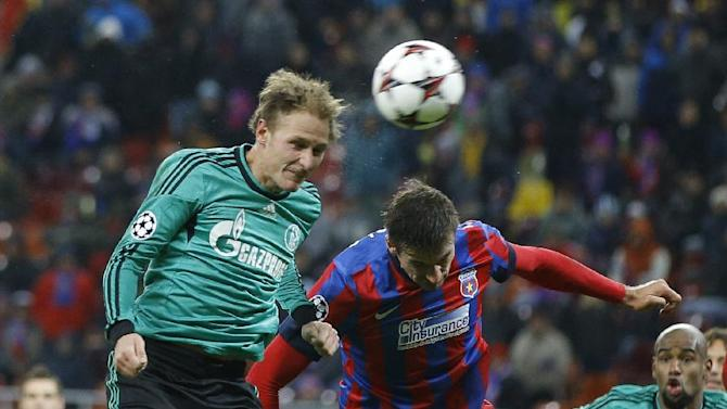 Schalke's Benedikt Hoewedes, left, tries to reach a high ball with Bucharest's Lukasz Szukala, during their Champions League Group E soccer match at the National Arena in Bucharest, Romania, Tuesday, Nov. 26, 2013